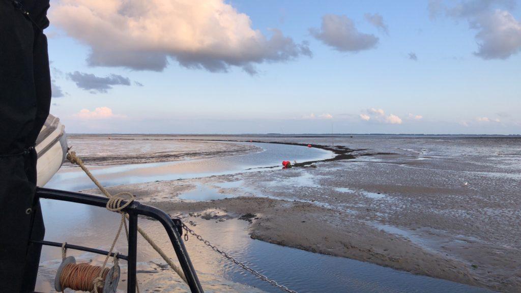 Met het zeilschip klipper nova cura droogvallenn in de haven van Schiermonnikoog met prachtig uitzicht op Groningse kust