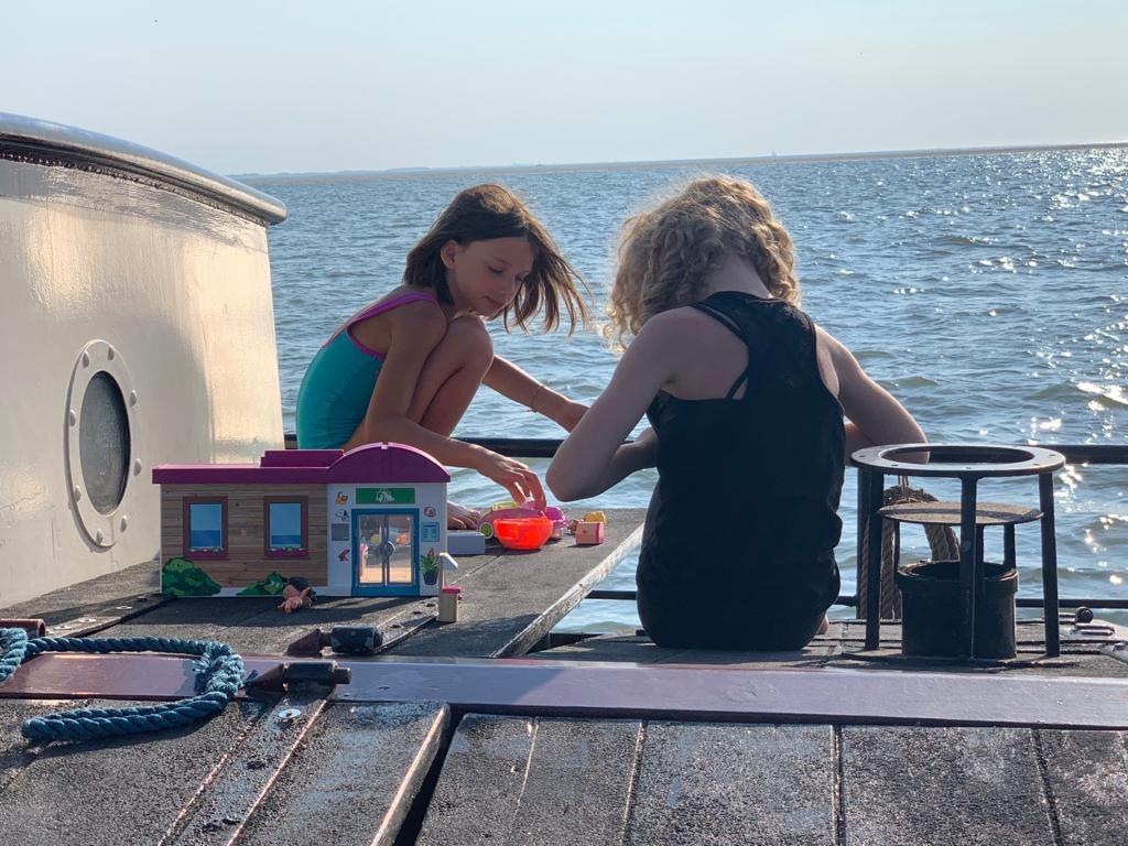 Kinderen spelen aan dek tijdens eilandhoppen op de waddenzee