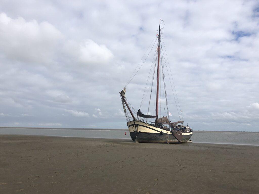 Droogvallen op het strand oostwad met het zeilschip klipper nova cura